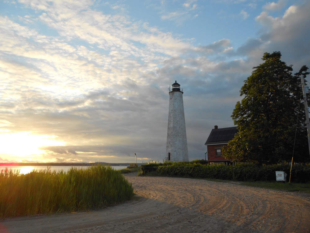 Sunset with the beach and Five Mile Point Lighthouse at Lighthouse Point Park in New Haven, CT.